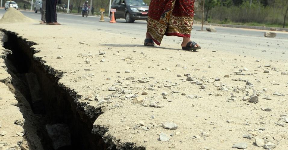 26.abr.2015 - Nepaleses andam em meio aos danos causados em estrada de Katmandu, no Nepal, um dia após o pior abalo sísmico do país desde 1934