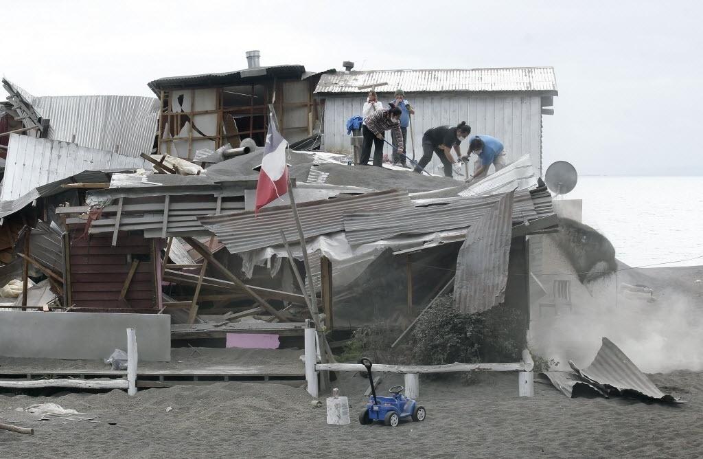 26.abr.2015 - Pessoas limpam telhado de casa parcialmente destruída pelo peso das cinzas do vulcão Calbuco, na cidade de Ensenada - sul do Chile