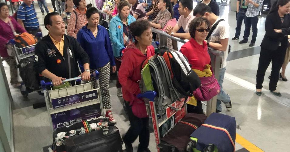 26.abr.2015 - Turistas chineses desembarcam em Chengdu, no sudoeste da China, após sobreviverem ao terremoto de magnitude 7.8 que devastou o Nepal. Ao todo, 198 passageiros estavam a bordo do voo de resgate a chineses
