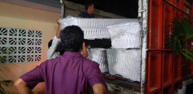 Funcionários carregam nove caixões em caminhão de uma igreja em Cilapac, na Indonésia, para serem entregues na ilha-prisão de Nusakambangan
