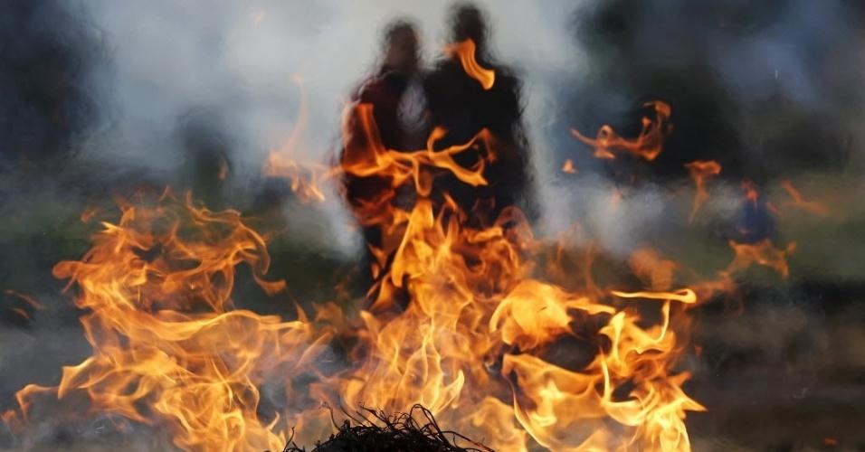27.abr.2015 - Família observa pira ardente durante cremação de um membro da família após terremoto em Bhaktapur ocorrido neste sábado (25). Funcionários do governo nepalês buscavam nesta segunda-feira (27) formas de conseguir ajuda externa para os desabrigados. Outras milhares de pessoas se deslocaram para regiões próximas de planícies