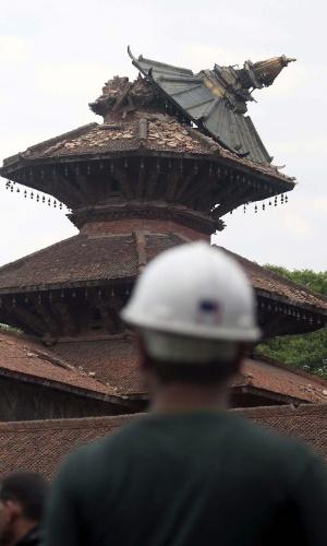 27.abr.2015 - Integrante de equipe de resgate observa o teto destruído de um edifício na praça Patan Durbar, em Katmandu, nesta segunda-feira (27). O Nepal foi atingido por um terremoto de 7,8 de magnitude no sábado (25), que deixou milhares de vítimas