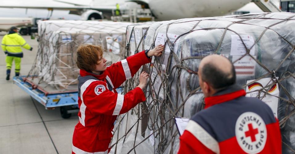 27.abr.2015 - Membros da Cruz Vermelha alemã preparam carga de ajuda humanitária para as vítimas do terremoto no Nepal em avião que embarca do Aeroporto de Berlim-Schönefeld, em Schönefeld, Brandemburgo