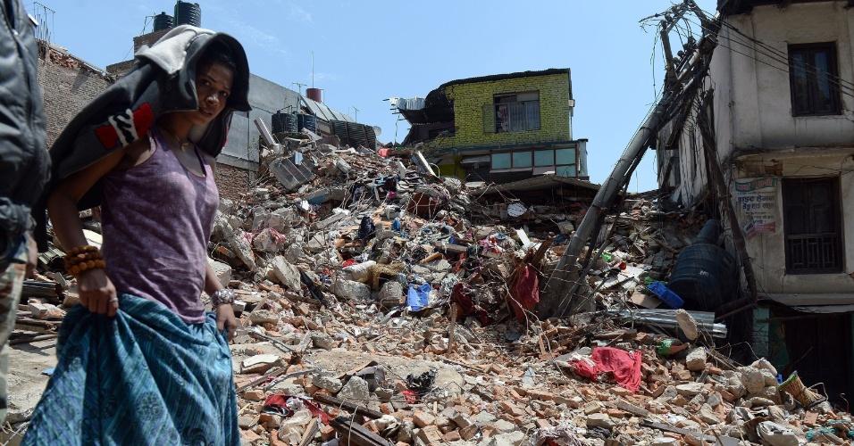 27.abr.2015 - Nepalesa passa por escombros de uma casa em Balaju, Katmandu, derrubada pelo terremoto de 7,8 de magnitude que dizimou partes da cidade no sábado (25). O fenômeno causou milhares de mortes, queda de monumentos históricos e a fuga em massa de turistas