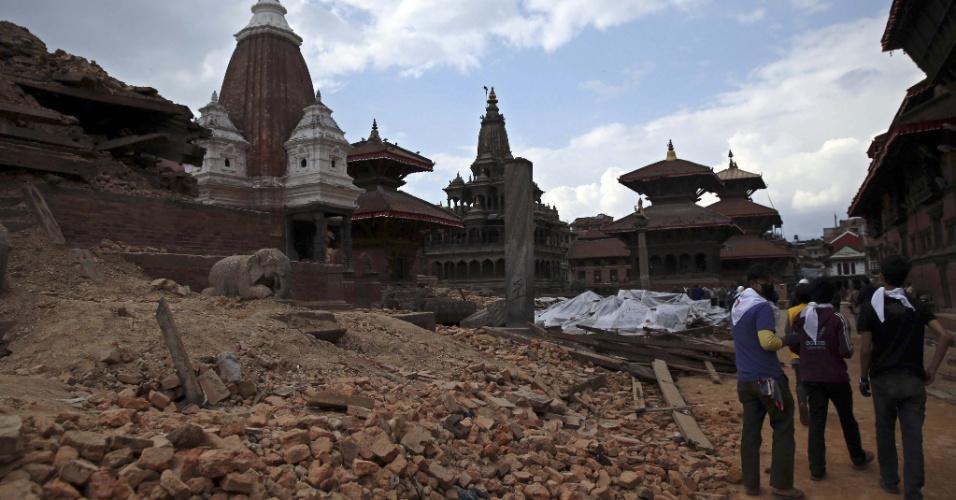 27.abr.2015 - Nepaleses caminham nesta segunda-feira (27) entre os escombros de estruturas afetadas em Katmandu pelo terremoto de magnitude 7,8 que atingiu o país no sábado (25). Equipes de resgate da Alemanha, dos Estados Unidos e da Índia estão chegando ao país para ajudar a buscar sobreviventes que ainda estejam presos sob os escombros