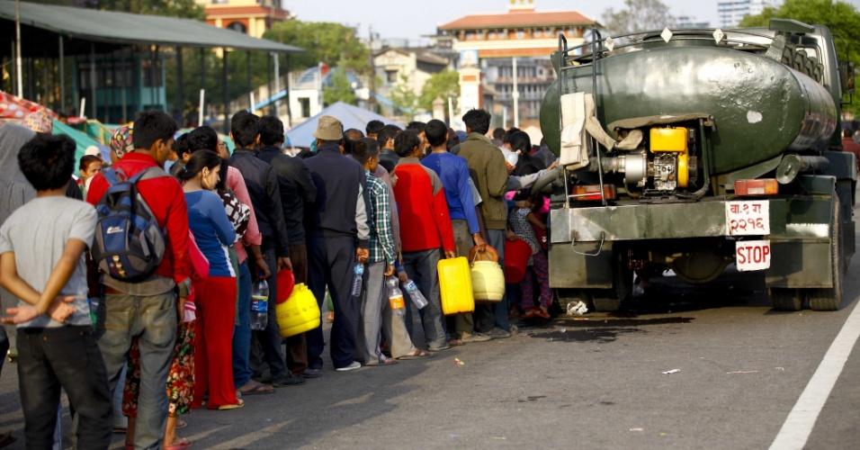27.abr.2015 - Nepaleses fazem fila para buscar água no Pavilhão Militar em Tundikhel, Katmandu, depois que parte da cidade foi arrasada por um terremoto e o recurso se tornou escasso. O tremor de magnitude 7,8 sacudiu várias partes do país, deixando milhares de mortos, feridos e desabrigados