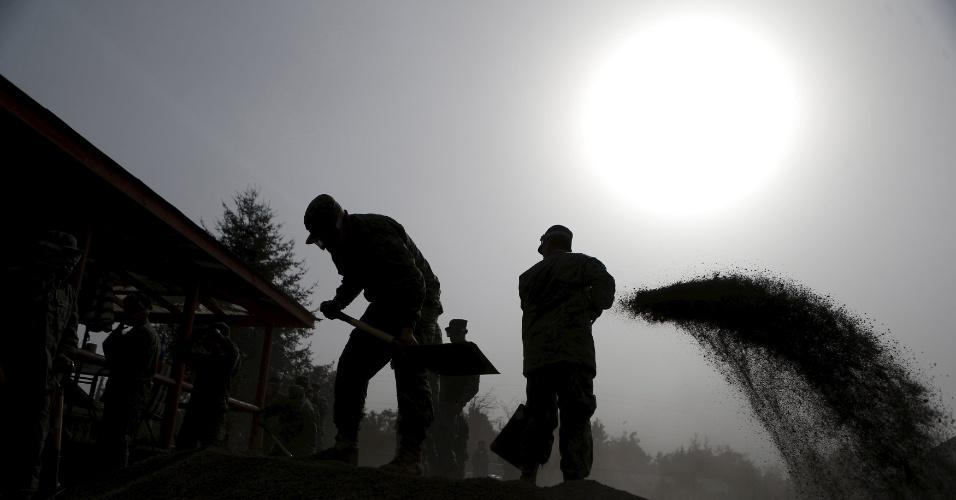 27.abr.2015 - Soldados removem cinzas de uma casa, próximo a Ensenada, região de Los Lagos, no sul do Chile, nesta segunda-feira (27). A região ficou coberta por cinzas após a erupção do vulcão Calbuco na semana passada