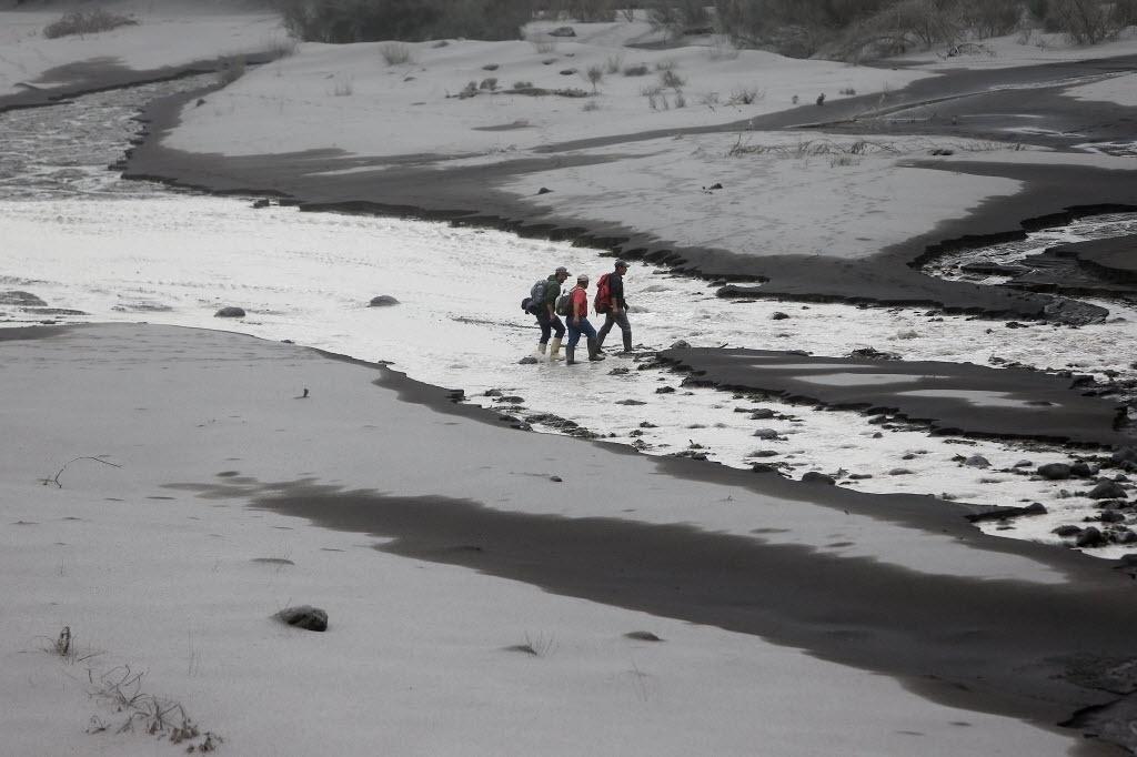 27.abr.2015 - Três homens cruzam o rio Hueñu Hueñu em cenário coberto pelas cinzas do vulcão Calbuco, em Ensenada, região de Los Lagos, no sul do Chile, nesta segunda-feira (27)