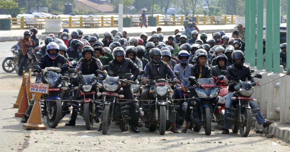 28.abr.2014 - Nepaleses formam fila para abastecer veículos em Katmandu. O terremoto de magnitude 7,8 que atingiu o Nepal no sábado (25) destruiu estruturas e pontos turísticos do país, além de provocar milhares de mortes e deixar centenas de milhares de desabrigados