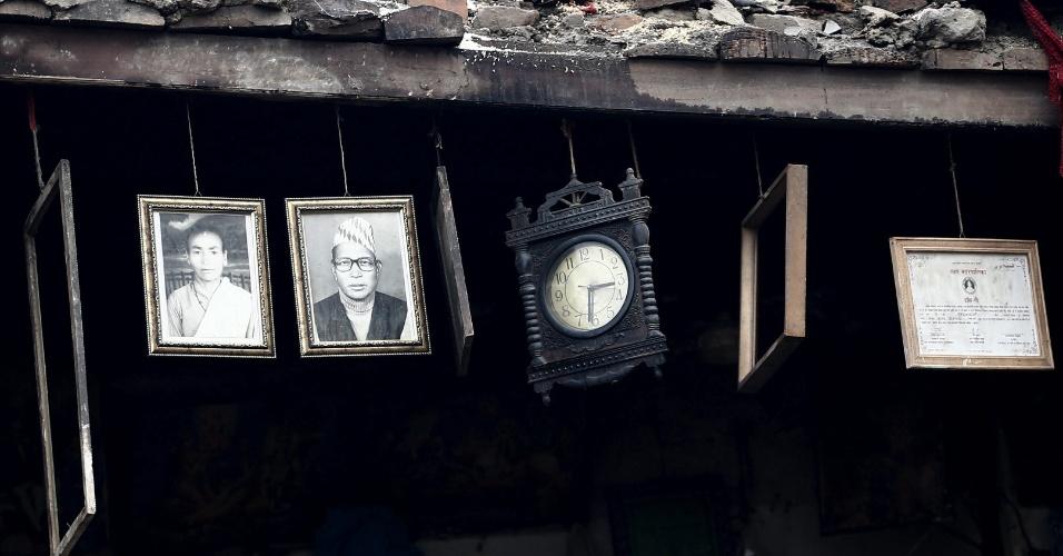 28.abr.2015 - Fotografias, um relógio e quadros permanecem intactos em meio aos escombros de propriedade em Bhaktapur, próximo à Katmandu, destruída pelo terremoto de magnitude 7,8 que sacudiu o Nepal no sábado (25), deixando milhares de mortos e centenas de milhares de desabrigados
