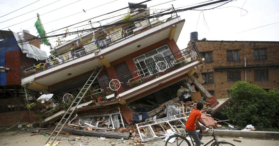 28.abr.2015 - Garoto observa casa em Katmandu, no Nepal, parcialmente destruída pelo terremoto.  Um tremor de magnitude 7,8 sacudiu o país no sábado (25) e causou milhares de mortes. Segundo a ONU, o terremoto afetou a vida de 8 milhões de pessoas