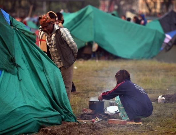 28.abr.2015 - Menina nepalesa cozinha em um campo montado acampamento montado em Katmandu. Os trabalhos de resgate continuam dificultados devido ao mau tempo e falta de estrutura do país para responder a um desastre dessa magnitude. A equipe das Nações Unidas para avaliação e coordenação em casos de desastre (UNDAC) advertiu que o tempo para encontrar pessoas com vida está acabando