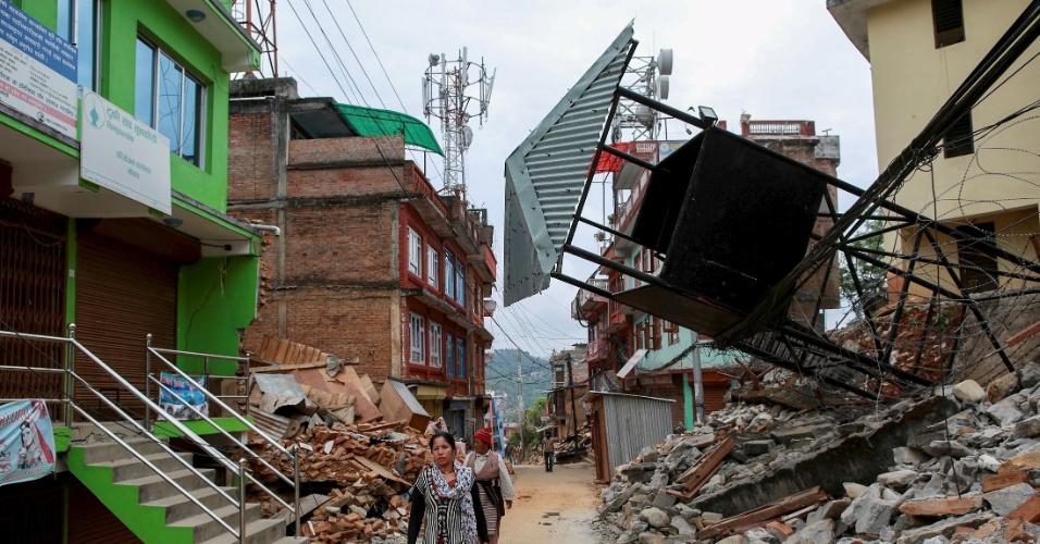 28.abr.2015 - Moradores caminham por rua cheia de destroços em Sindhupalchowk, no Nepal, atingida pelo terremoto de magnitude 7,8 que sacudiu o país no sábado (25). A tragédia causou milhares de mortes e afetou 8 milhões de pessoas, segundo a ONU