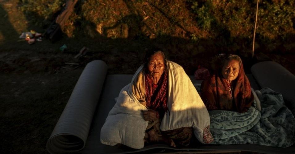 28.abr.2015 - Moradores da vila Paslang, em Gorka, sentam em abrigo improvisado perto de uma área devastada depois do terremoto de sábado (25) que atingiu o Nepal