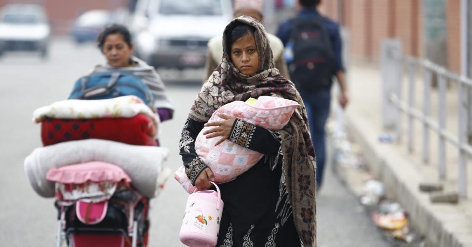 28.abr.2015 - Mulher carrega criança enquanto sua mãe leva o carrinho do bebê cheio de cobertores em Katmandu, no Nepal. Um terremoto de magnitude 7,8 atingiu o país no sábado (25), causando destruição e milhares de mortes. Com medo de novos tremores, milhares de moradores da cidade deixaram suas casas