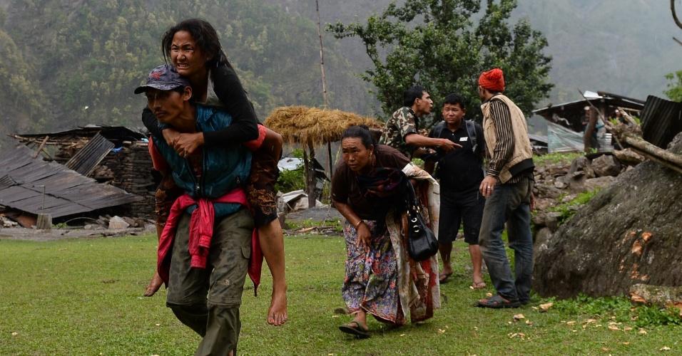 28.abr.2015 - Nepalesa ferida e sua família é resgatada pelo exército indiano em Gorkha, no Nepal. Equipes de resgate lutam para chegar às comunidades remotas que foram devastadas pelo terremoto de 7,8 de magnitude que matou milhares de pessoas
