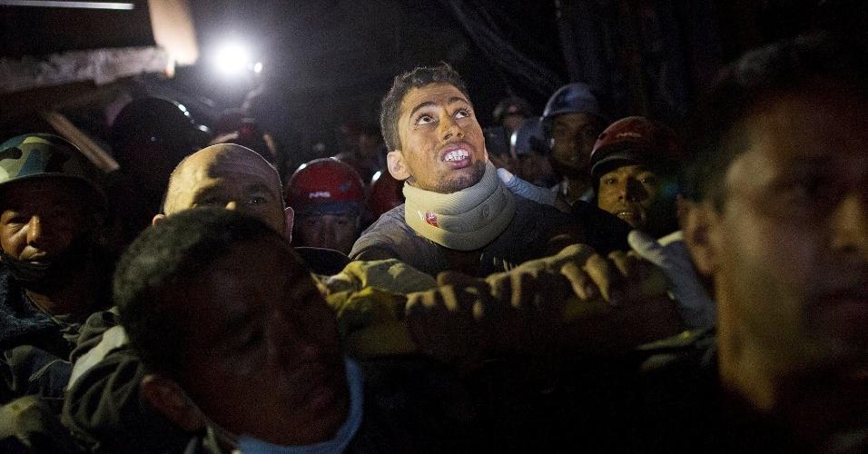 28.abr.2015 - Rishi Khanal, 28, é carregado por policiais nepaleses após ser resgatado por equipes francesas de um prédio que desabou durante o terremoto no último sábado em Katmandu, no Nepal, nesta terça-feira (28). Ele teria ficado preso sob os escombros durante 80 horas em um quarto com outras três pessoas mortas