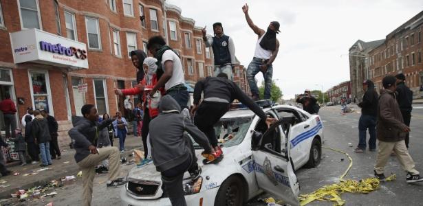 Manifestantes sobem em carro da polícia de Baltimore, em Maryland (EUA)