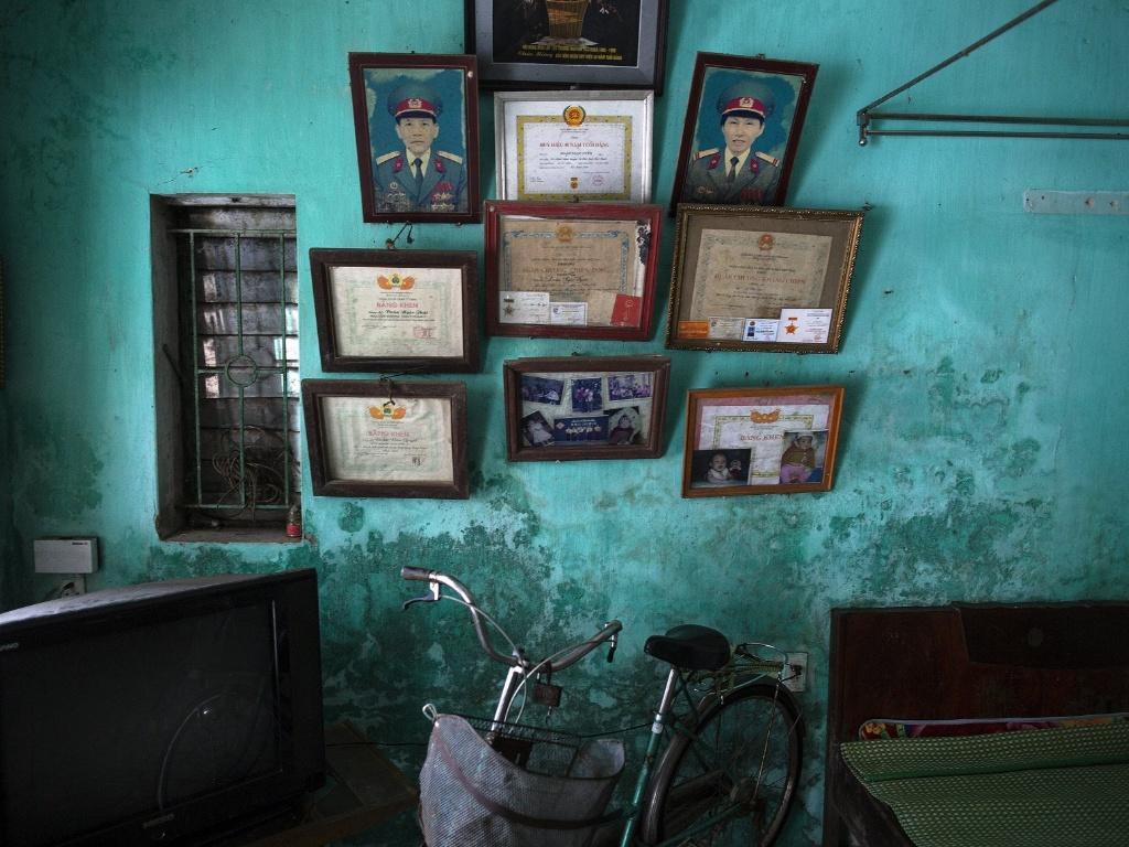 10.abr.2015 - Fotos e diplomas dos ex-soldados Doan Ngoc Uyen e Le Thi Teo decoram a parede da casa da família na província de Thai Binh, no Vietnã. A filha do casal, Doan Thi Hong Gam, sofre de severos problemas físicos e mentais. Seu pai foi exposto ao agente laranja ao lutar durante a guerra