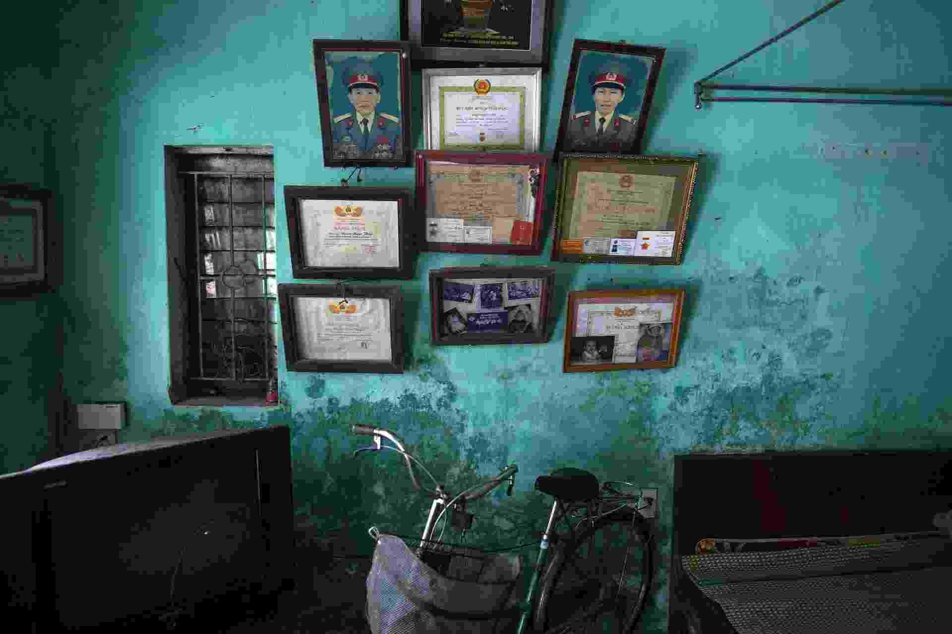 10.abr.2015 - Fotos e diplomas dos ex-soldados Doan Ngoc Uyen e Le Thi Teo decoram a parede da casa da família na província de Thai Binh, no Vietnã. A filha do casal, Doan Thi Hong Gam, sofre de severos problemas físicos e mentais. Seu pai foi exposto ao agente laranja ao lutar durante a guerra - Damir Sagolj/Reuters