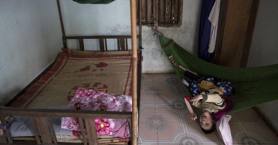 11.abr.2015 - Phan Van Lam deita em rede na casa de sua família em Quang Binh, no centro do Vietnã. O pai de Lam, um ex-combatente do Exército do Vietnã do Norte, viveu em áreas contaminadas pelo agente laranja. Seu filho tem graves danos  cerebrais