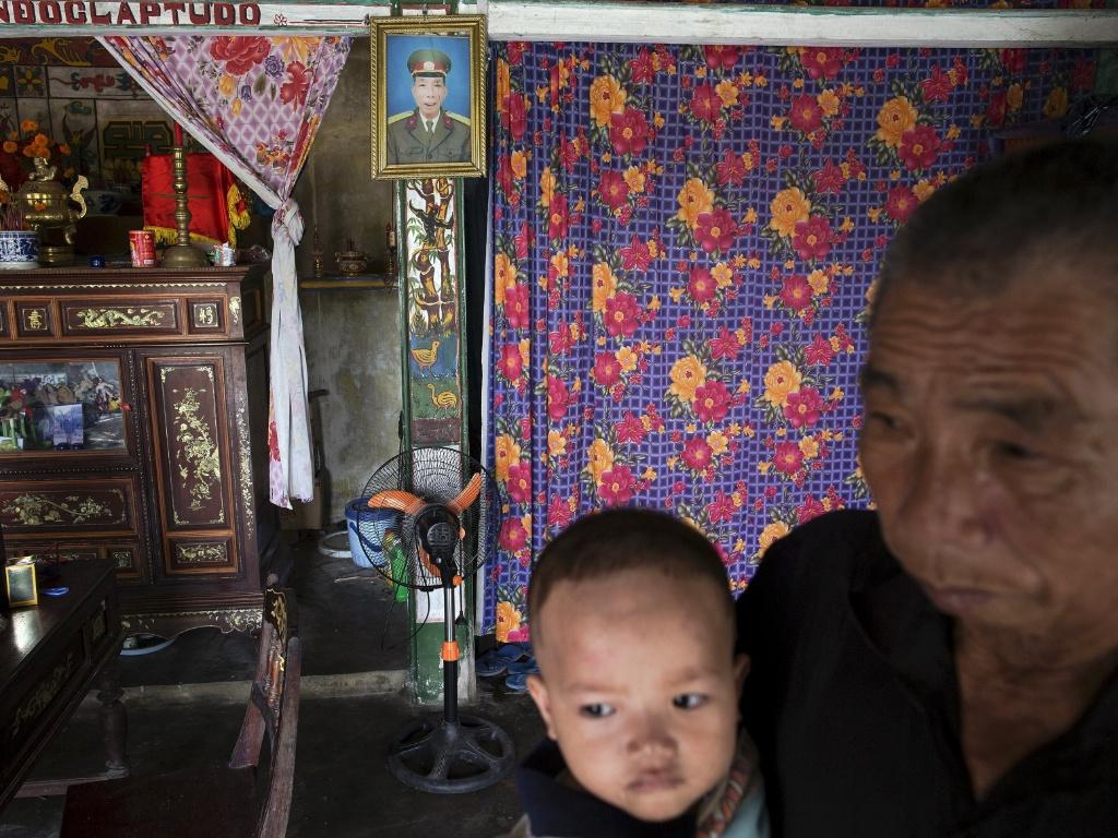 11.abr.2015 -Doan Tue carrega a filha em sua casa em Truc Ly, no Vietnã; ao fundo, na parede, foto dele com uniforme militar. Doan serviu na Guerra do Vientã e viveu em áreas contaminadas pelo agente laranja. Dois de seus filhos nasceram com sérios problemas de saúde