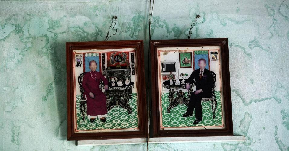12.abr.2015 - Fotos desgastadas de Dang Van Sanh (dir) e sua mulher, Nguyen Thi Thin, ficam penduradas na parede da casa da família no vilarejo de Le Son Bac, ao norte de Danang, no Vietnã. Dang Van Sanh foi diretamente atingido pelo agente laranja enquanto combatia nas selvas durante a Guerra do Vietnã e morreu mais tarde de câncer na gargante. Dois de seus quatro filhos morreram logo após nascer. Seu filho Dang Van Son tem deficiências