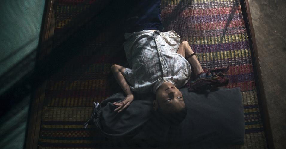 12.abr.2015 - Le Dang Ngoc Hung, 16, descansa sob mosquiteiro na casa de sua família no vilarejo de Phuoc Thai, próximo a Danang, no Vietnã. O avô do adolescente, Le Van Dan, ex-soldado de artilharia do Exército de Vietnã do Sul, disse ter sido exposto diretamente ao agente laranja