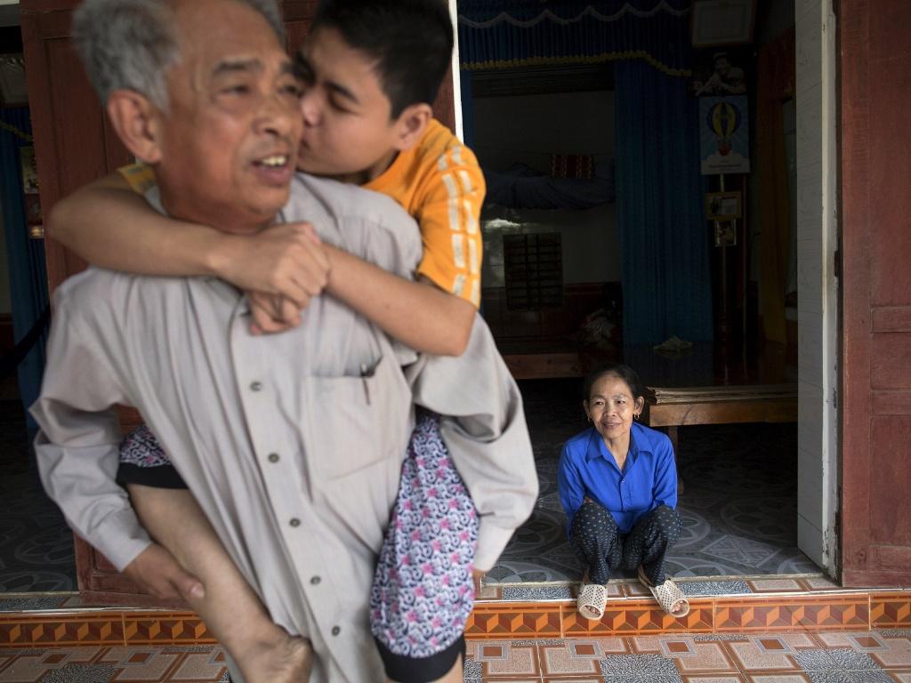 11.abr.2015 - O ex-soldado Do Duc Diu é beijado pelo filho Do Thi Nga, enquanto sua mulher se senta à porta de casa em Quang Binh, no centro do Vietnã. Doze de seus quinze filhos morreram de doenças causadas pela exposição do ex-soldado ao agente laranja, segundo médicos. Do serviu como soldado do Exército do Vietnã do Norte nos anos 1970 em áreas contaminadas pelo agente. Ele só soube dos efeitos adversos quando seu último filho nasceu, em 1994