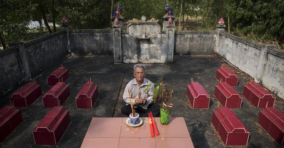 11.abr.2015 - O ex-soldado Do Duc Diu reza no cemitério em que doze de seus quinze filhos estão enterrados, próximo a sua casa em Quang Binh, no centro do Vietnã. Os filhos morreram em decorrência de doenças provocadas pela exposição do pai ao agente laranja, segundo médicos
