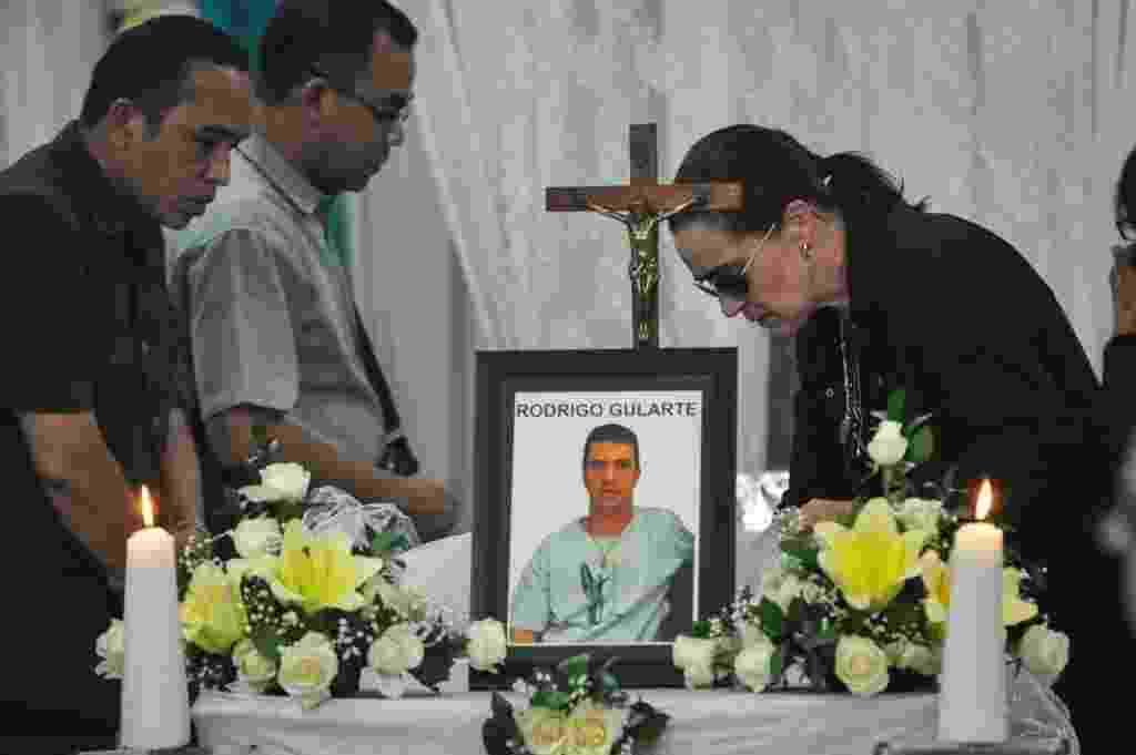 29.abr.2015 - Angelita Muxfedlt, prima do brasileiro Rodrigo Gularte, executado na Indonésia na terça-feira (28) sob acusação de tráfico de drogas, olha o corpo do primo dentro de um caixão. O corpo de Gularte foi levado a Jacarta, onde uma missa será realizada na capela do hospital. Nos próximos dias, ele erá preparado para ser levado ao Brasil, para ser enterrado em Curitiba  - Veri Sanovri/Xinhua