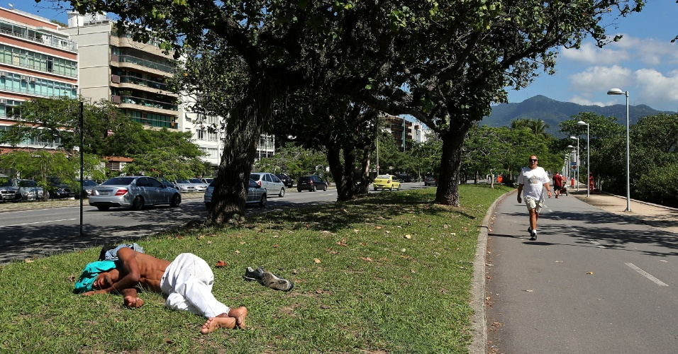 29.abr.2015 - Homem dorme na rua nos arredores da Lagoa Rodrigo de Freitas, na zona sul do Rio de Janeiro, enquanto pedestres e ciclistas circulam pela pista destinada a atividades de lazer