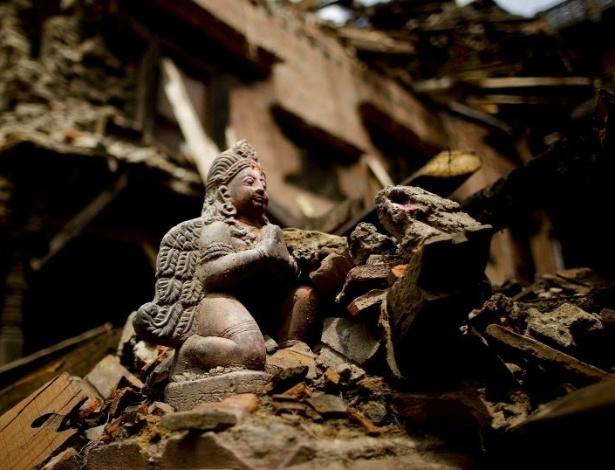 29.abr.2015 - Pequena escultura permanece intacta entre escombros de casas e edifícios destruídos no terremoto ocorrido sábado (25) em Katmandu, Nepal. Cerca de 340 mil pessoas deixaram o vale de Katmandu por medo de novos tremores e surtos de doenças, disse a polícia nesta quarta-feira (29). O número de mortos no terremoto ultrapassou 5.000 e os feridos superaram 10.000 pessoas, enquanto o número de desabrigados está em 450.000 pessoas