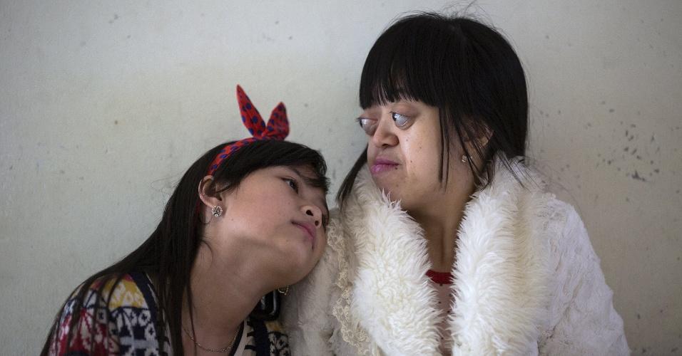 8.abr.2015 - Nguyen Thi Van Long (dir) e sua melhor amiga, Dinh Thi Huong, que é surda-muda, passam tempo juntas do hospital Friendship, especializado em vítimas do agente laranja, próximo a Hanói, no norte do Vietnã. Os pais das duas moças era soldados que foram expostos ao agente durante a Guerra do Vietnã. O hospital abriga cerca de 120 crianças e 60 veteranos