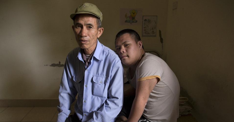 8.abr.2015 - O ex-soldado Nguyen Hong Phuc, 63, senta ao lado com seu filho Nguyen Dinh Loc, 20, que está se recuperando de uma cirurgia de um tumor no hospital Friendship, que atende vítimas do agente laranja, próximo a Hanói, no norte do Vietnã. Nguyen Dinh Loc tem sérios problemas e físicos que médicos atribuem à exposição do pai ao agente laranja