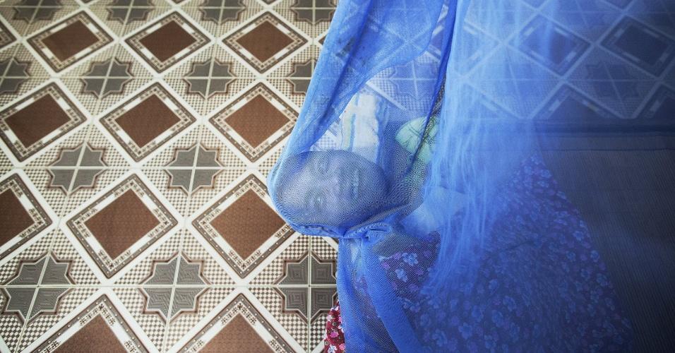 9.abr.2015 - Lai Van Manh sorri deitado sob um mosqueteiro em sua casa em Tuong An, na província de Thai Binh, no norte do Vietnã. Seu pai, um ex-agente de inteligência do Exército do Vietnã do Norte, disse que serviu em áreas contaminadas pelo agente laranja. Dois de seus filhos têm deficiências mentais e físicas