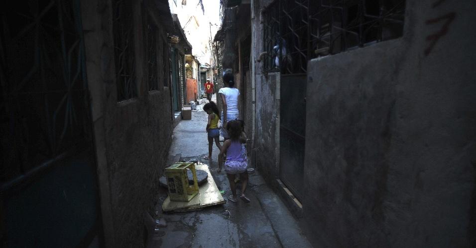 28.abr.2015 - Moradores caminham por beco da comunidade Roquette Pinto, uma das 16 do Complexo de Favelas da Maré, na zona norte do Rio de Janeiro. A favela está ocupada pela PM desde o dia 1º de abril e vai receber a primeira UPP (Unidade de Polícia Pacificadora) da Maré