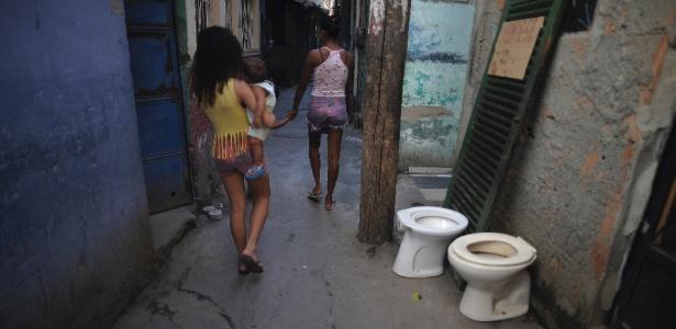 Moradores caminham por beco da comunidade Roquette Pinto, uma das 16 do Complexo de Favelas da Maré, na zona norte do Rio de Janeiro