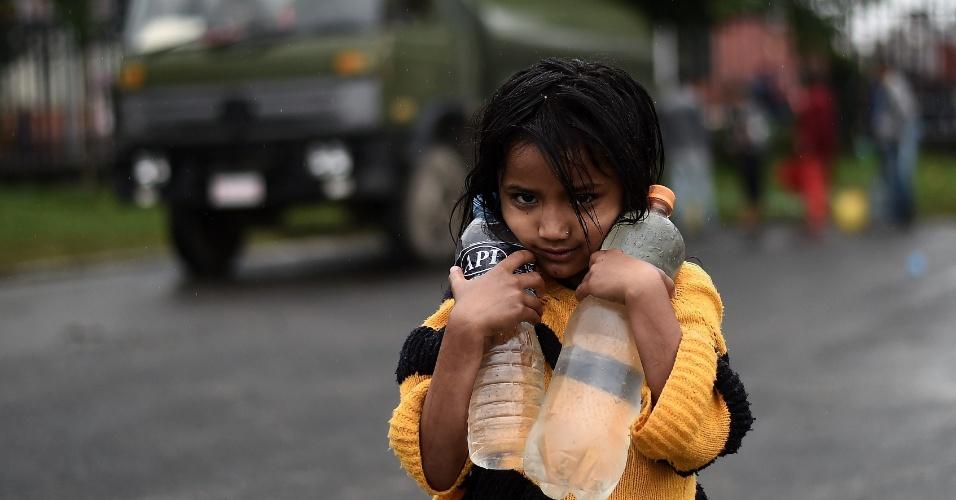 30.abr.2015 - Criança nepalesa carrega garrafas d'água para a tenda improvisada que abriga sua família em Katmandu, no Nepal, cidade que sofre com o rastro de destruição causado pelo terremoto que atingiu o país no último sábado (25). A ONU (Organização das Nações Unidas) emitiu um apelo de emergência pedindo a solidariedade de outros países. Há carência de doações de água potável, alimentos e remédios