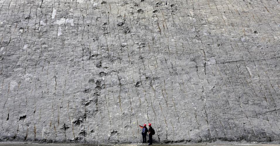 30.abr.2015 - Dois homens se deparam com uma rocha que apresentam marcas de pegadas de dinossauro no sítio arqueológico Cal Orcko (Parque Cretácico de Sucre), em Sucre, na Bolívia, nesta quinta-feira (30). O local reserva relíquias do período paleontológico no país sul-americano
