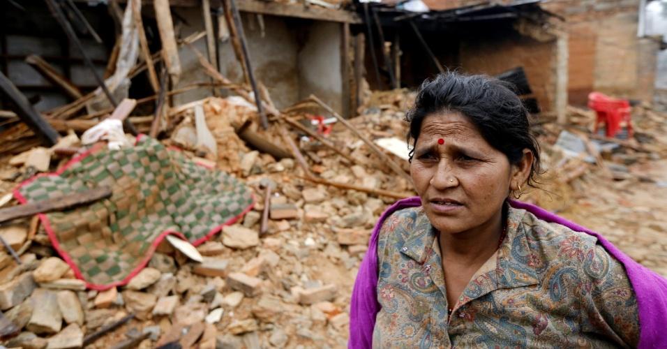 30.abr.2015 - Moradora de Gorkha, província do epicentro do terremoto que afetou grande parte do Nepal, passa diante dos destroços de sua casa, na manhã desta quinta-feira (30). A ONU lançou um apelo a países para que contribuam com abrigo, alimentação e cuidados médicos aos sobreviventes do tremor ocorrido no último sábado, e que causou a morte de mais de 5.000 pessoas no Nepal, sudoeste da China e norte da Índia