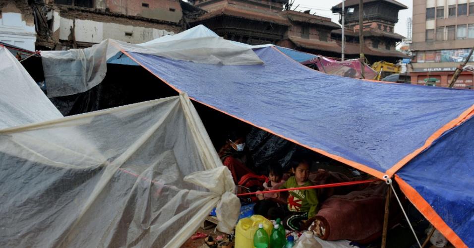 30.abr.2015 - Moradores de Katmandu descansam na manhã desta quinta-feira (30) em abrigo improvisado perto de edifícios danificados pelo terremoto que atingiu a cidade no sábado. A ONU lançou um apelo a países para que contribuam com abrigo, alimentação e cuidados médicos aos sobreviventes do tremor de intensidade 7,8 que matou mais de 5.000 pessoas no Nepal, sudoeste da China e norte da Índia