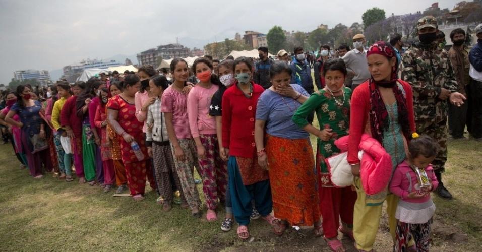 30.abr.2015 - Mulheres nepalesas e crianças esperam na fila para receber alimentos distribuídos por uma organização não-governamental no centro de Katmandu, no Nepal. A ONU lançou um apelo para arrecadar US$ 415 milhões para ajudar na compra de alimentos, água e cuidados médicos para  sobreviventes do terremoto em meio a raiva dos habitantes diante da incapacidade do governo para lidar com um desastre que matou mais de 6.000 pessoas