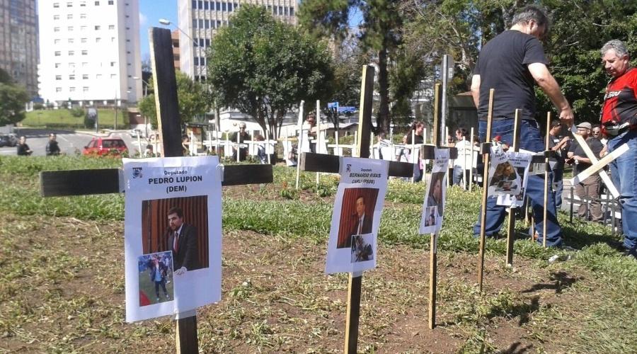 1º.mai.2015 - Manifestantes cravam em praça no Centro Cívico cruzes com fotos dos deputados que votaram na última quarta-feira (29) a favor do projeto de lei que altera a previdência estadual