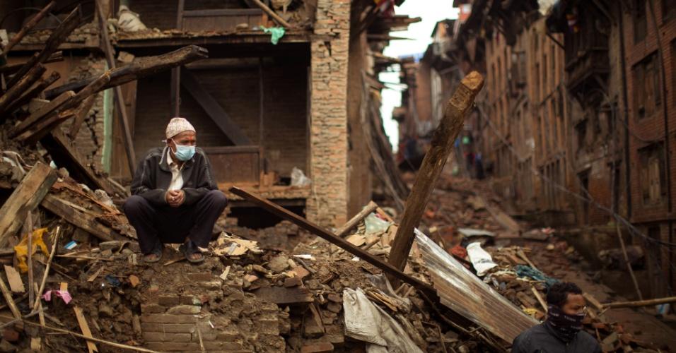 1º.mai.2015 - Moradores observam as ruínas, enquanto militares ajudam no resgate de vítimas do terremoto do último sábado (25) no vilarejo nepalês de Bhaktapur, próximo a Katmandu. O tremor de magnitude 7,8 causou mais de 6.200 mortes no país, que encontra uma crise humanitária pela falta de recursos para lidar com a tragédia