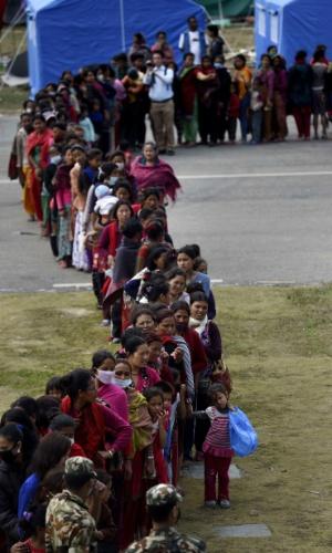 1º.mai.2015 - Nepalesas fazem fila nesta sexta-feira (1º) para receber cesta básica diária de alimentos, distribuída pelo exército em acampamento montado em Katmandu onde os moradores da cidade que perderam suas casas vivem após o terremoto do último sábado (25). O tremor de magnitude 7,8 causou mais de 6.200 mortes no país, que encontra uma crise humanitária pela falta de recursos para lidar com a tragédia