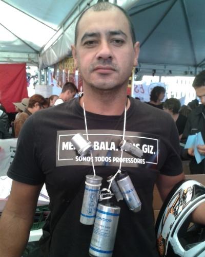 1º.mai.2015 - O servidor público Jairo Gomes Veloso exibe espécie de colar que fez com cápsulas de bomba de gás lacrimogênio que recolheu no confronto entre a Polícia Militar e professores na quarta-feira (29). Ele conta que foi atingido por balas de borracha nas pernas. Veloso participa de protesto na praça 19 de Dezembro, no Centro Cívico, em Curitiba, nesta sexta-feira (1)