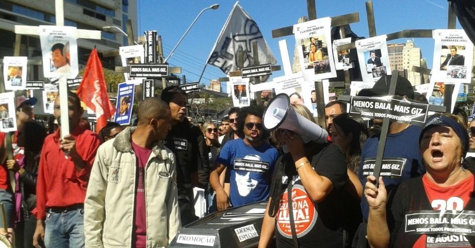 1.mai.2015 - Vestidos de preto, manifestantes carregam caixão e cruzes durante protesto na manhã na avenida Cândido de Abreu, no Centro Civico, em Curitiba. Eles protestam contra a repressão policial e o governo estadual