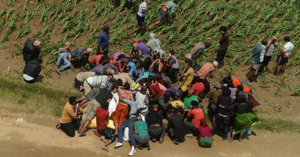 2.mai.2015 - Moradores de Kharibot, que sobreviveram ao terremoto que atingiu o Nepal no sábado passado (25), disputam mantimentos de ajuda emergencial descarregada por um helicóptero do exército indiano neste sábado (2). O governo nepalês descartou a possibilidade de encontrar mais sobreviventes nos escombros. O terremoto matou mais de 6.700 pessoas e devastou o país