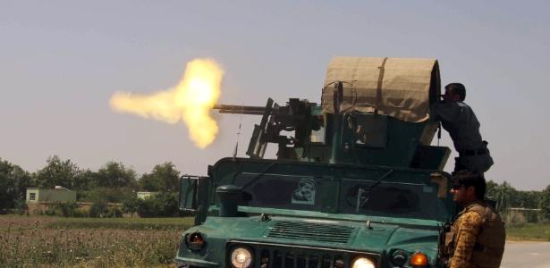 Policial em um carro militar atira contra insurgentes do taleban na província de Kunduz, no Afeganistão